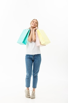 Portrait d'une belle jeune femme posant avec des sacs à provisions, isolé sur fond blanc