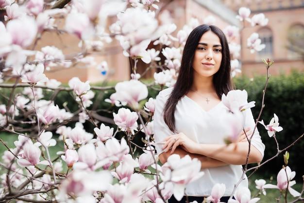 Portrait d'une belle jeune femme près de magnolia avec des fleurs.