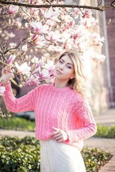 Portrait d'une belle jeune femme près d'un magnolia. printemps.