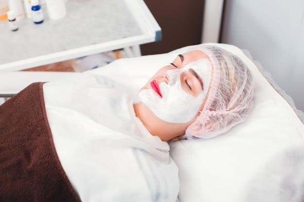 Portrait de la belle jeune femme qui applique un masque facial. procédure cosmétique dans le salon de spa. soins de la peau du visage.