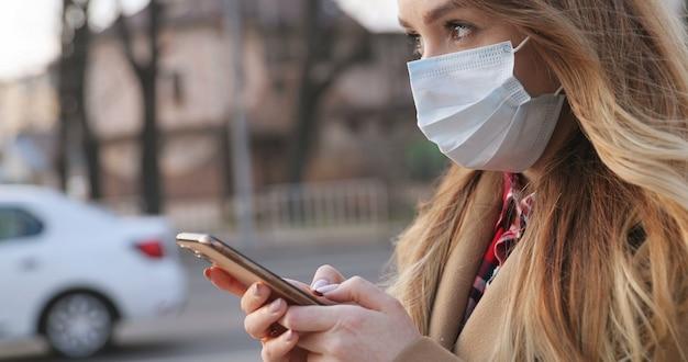 Portrait de la belle jeune femme de race blanche dans un masque médical à l'aide de son smartphone en plein air. message de texto de jolie fille sur le téléphone pendant la pandémie à la rue. concept de pandémie, épidémie de coronavirus.
