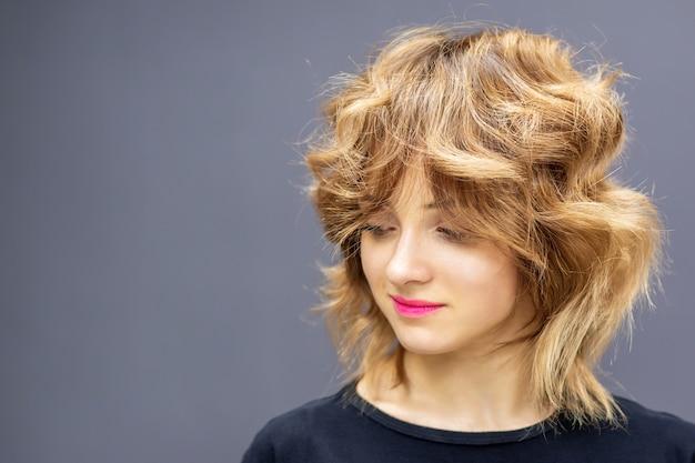 Portrait de la belle jeune femme de race blanche regardant vers le bas avec de longs cheveux roux ondulés sur un mur de couleur grise