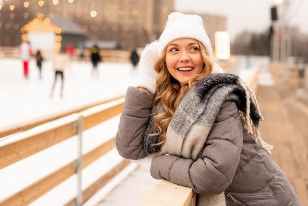 Portrait de la belle jeune femme sur le rang de glace de noël festif. dame portant des vêtements tricotés chauds d'hiver.