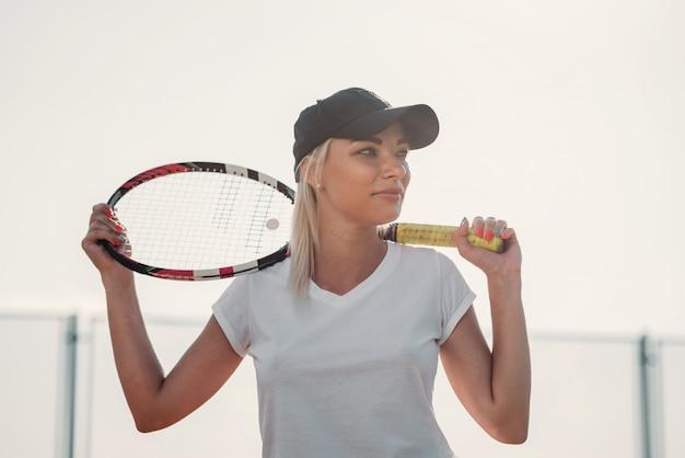 Portrait de la belle jeune femme avec une raquette de tennis sur un court