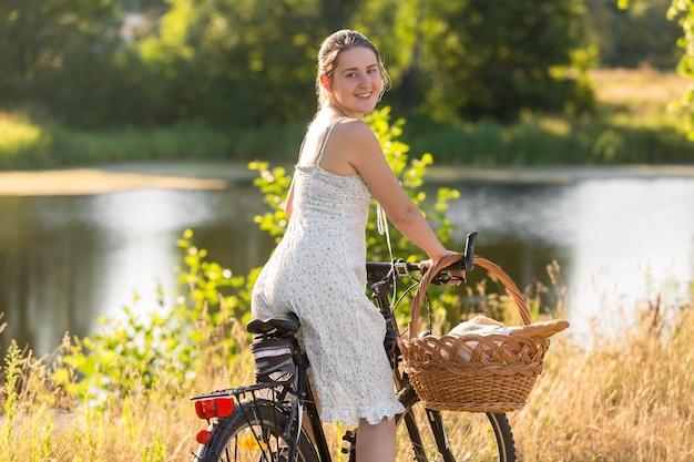 Portrait de belle jeune femme en robe courte à vélo au bord du lac au coucher du soleil