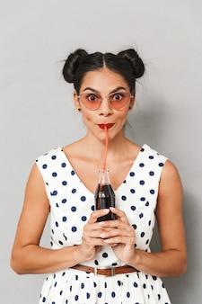 Portrait d'une belle jeune femme en robe d'été et lunettes de soleil isolées, tenant une bouteille avec une boisson gazeuse