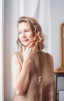 Portrait de la belle jeune femme en robe de lin près de la fenêtre, concept de beauté naturelle éco