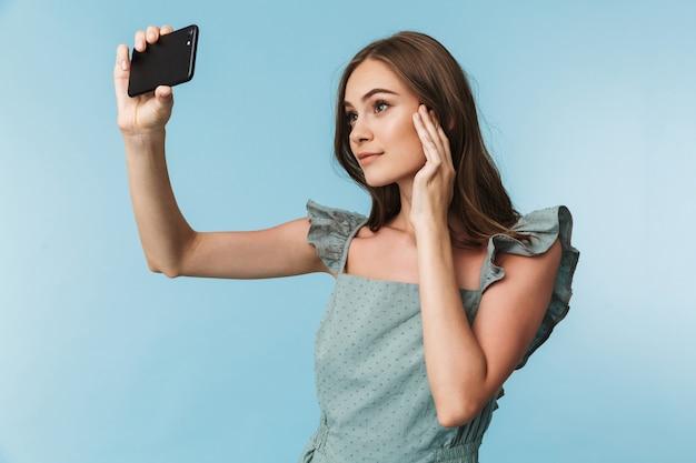 Portrait d'une belle jeune femme en robe prenant un selfie