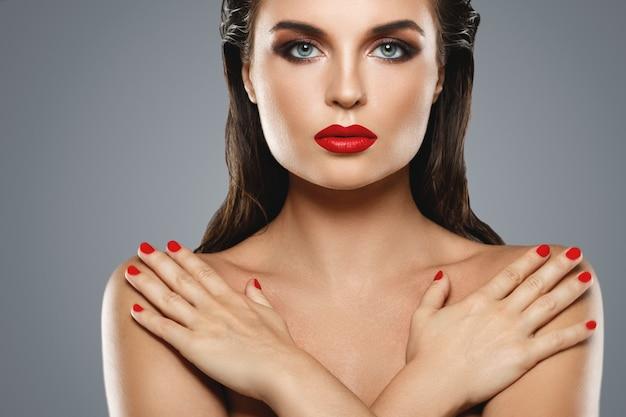 Portrait de la belle jeune femme avec un rouge à lèvres et du vernis à ongles