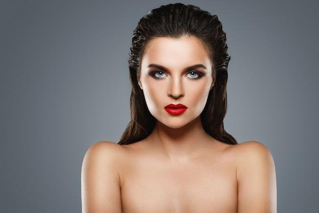 Portrait de la belle jeune femme avec un rouge à lèvres rouge