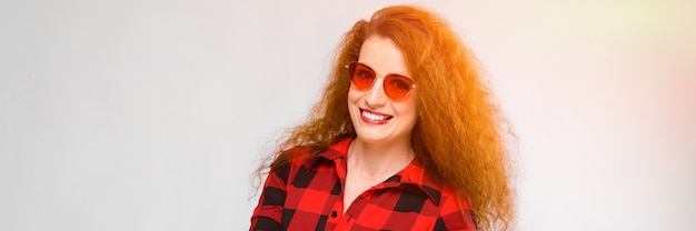 Portrait de belle jeune femme rousse belle lunettes de soleil souriant avec les mains ouvertes