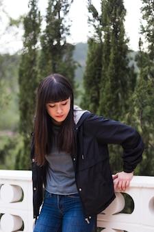 Portrait de la belle jeune femme s'appuyant sur la balustrade