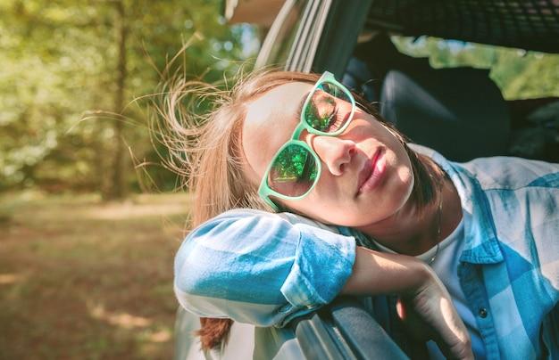Portrait d'une belle jeune femme avec sa tête au-dessus d'une voiture fenêtre ouverte lors d'un voyage. concept de détente et de nature.