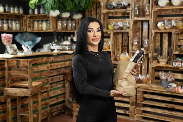 Portrait d'une belle jeune femme avec un sac en papier dans ses mains dans un magasin d'aliments naturels