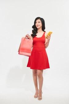 Portrait belle jeune femme avec des sacs à provisions et en regardant un téléphone mobile