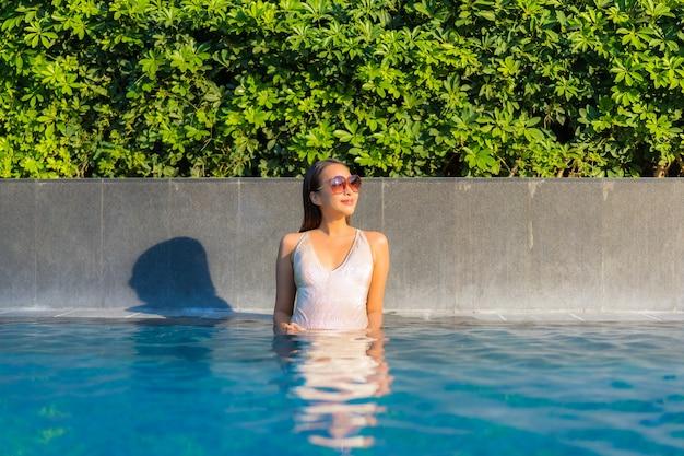 Portrait de la belle jeune femme se détendre à la piscine