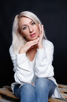 Portrait d'une belle jeune femme séduisante dans un pull blanc aux yeux bleus et aux longs cheveux blonds.
