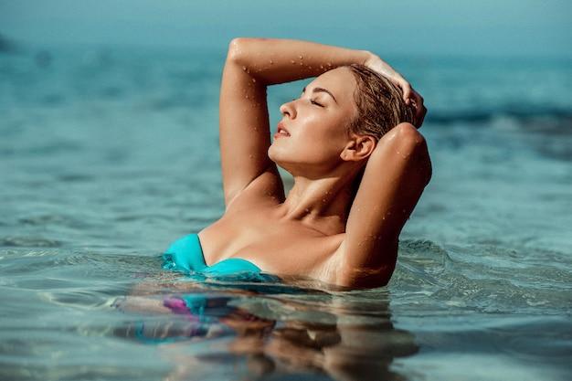 Portrait d'une belle jeune femme sensuelle en eau de mer se bouchent. mode