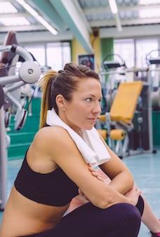 Portrait d'une belle jeune femme avec une serviette au repos assise sur le sol du centre de remise en forme après une dure journée d'entraînement