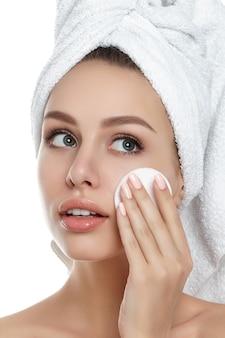 Portrait de la belle jeune femme avec une serviette sur ses cheveux, nettoyer le maquillage de son visage avec un tampon cosmétique isolé. nettoyage du visage, peau parfaite, concept de soins de la peau et de cosmétologie