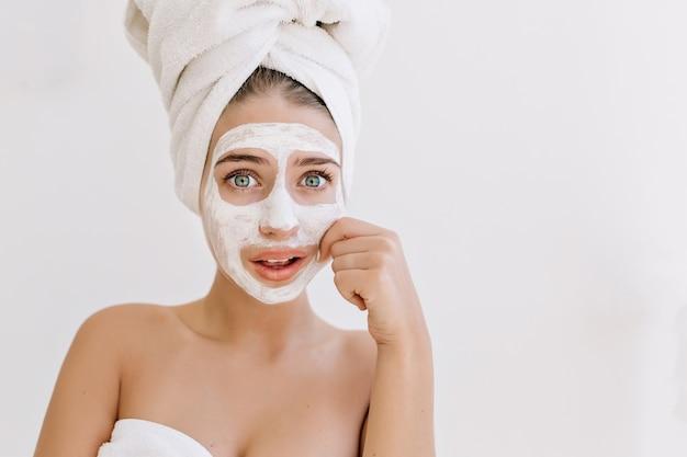 Portrait de la belle jeune femme avec des serviettes après le bain prendre un masque cosmétique et s'inquiète pour sa peau.