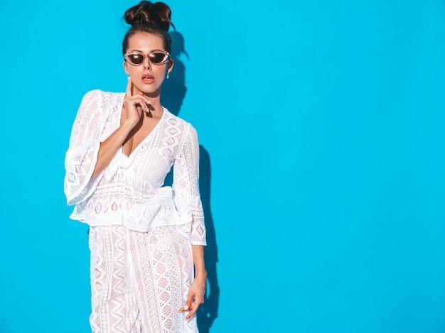 Portrait de la belle jeune femme sexy avec une coiffure de goule. fille à la mode dans des vêtements de costume hipster blanc d'été décontracté dans des lunettes de soleil. modèle chaud isolé sur bleu