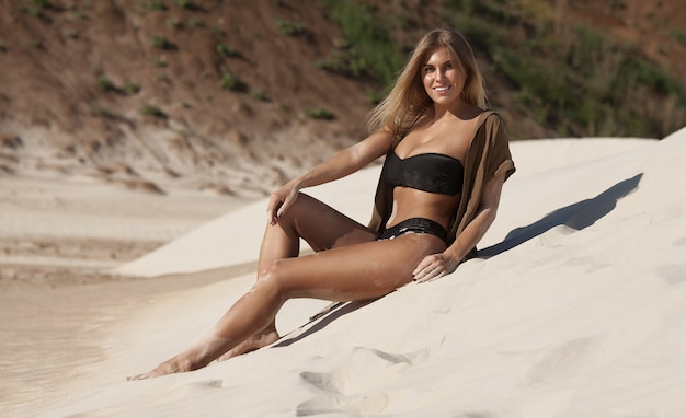 Portrait de la belle jeune femme sexy sur le sol de sable sur le soleil à l'extérieur