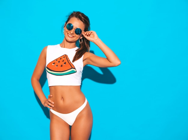 Portrait de la belle jeune femme sexy souriante en sous-vêtements d'été blanc et sujet. fille branchée à lunettes de soleil. femme positive qui devient folle. modèle drôle isolé
