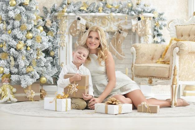 Portrait d'une belle jeune femme avec son fils posant dans une chambre décorée pour les vacances de noël