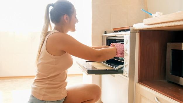 Portrait d'une belle jeune femme souriante aux cheveux longs prenant un plat de cuisson avec des biscuits chauds fraîchement sortis du four. femme au foyer cuisson à la maison