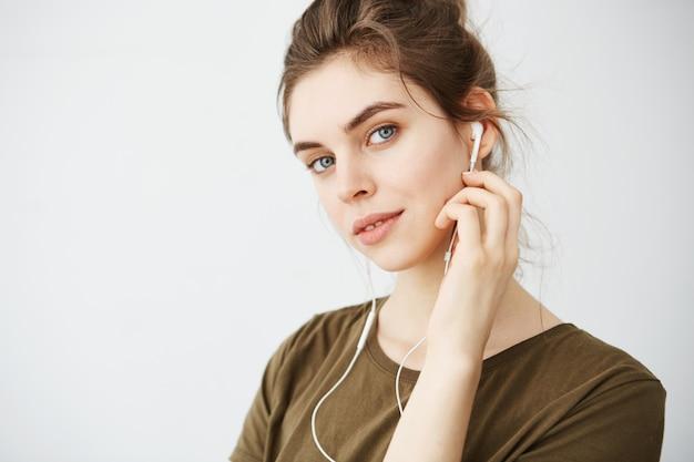 Portrait de la belle jeune femme souriante, écouter de la musique dans les écouteurs sur fond blanc.