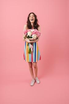 Portrait de la belle jeune femme souriante joyeuse et heureuse posant isolée sur un mur rose tenant des fleurs