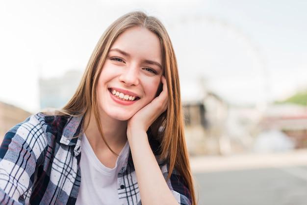 Portrait de la belle jeune femme souriante regardant la caméra