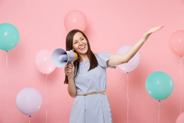 Portrait d'une belle jeune femme souriante en robe bleue tenant un mégaphone pointant la main de côté sur fond rose avec des ballons à air colorés. fête d'anniversaire, concept d'émotions sincères.