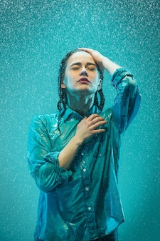 Le portrait de la belle jeune femme sous la pluie