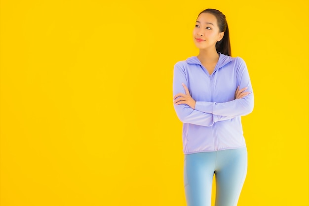 Portrait belle jeune femme sport asiatique prête pour l'exercice sur jaune