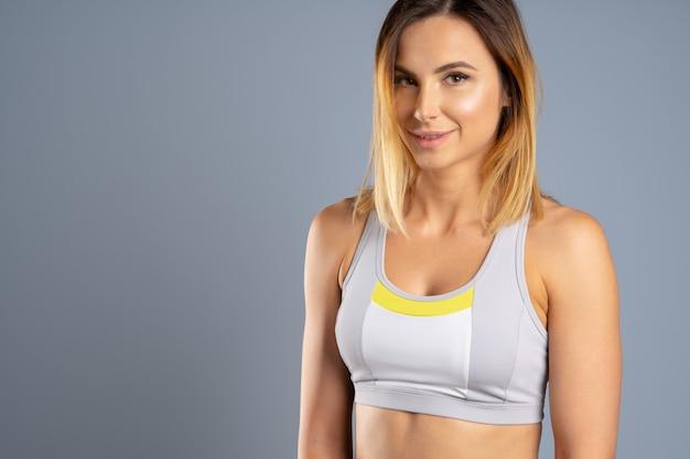 Portrait d'une belle jeune femme sportive sur fond gris