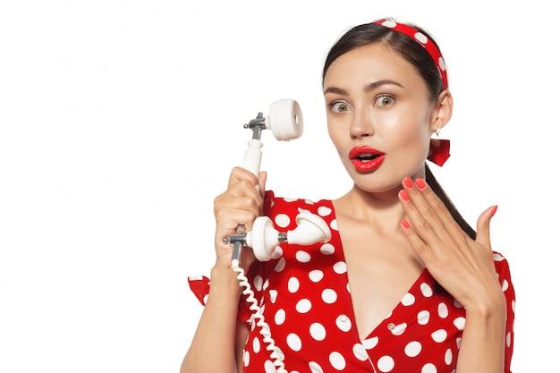 Portrait de la belle jeune femme avec un téléphone, habillé dans un style pin up.