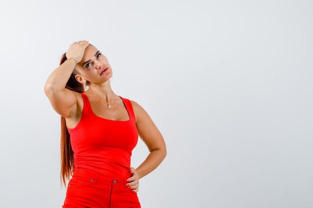 Portrait de la belle jeune femme tenant la main sur le front, regardant en débardeur rouge, pantalon et à la vue de face pensive