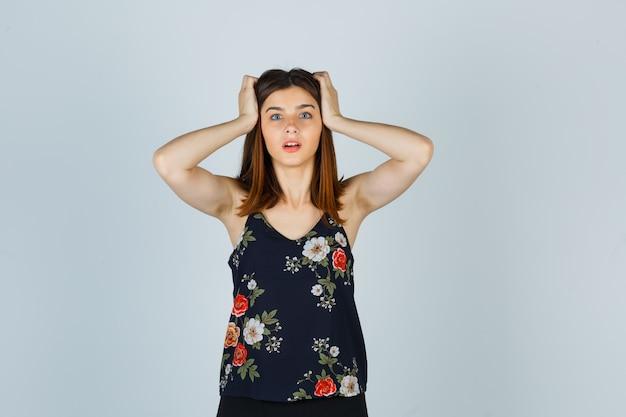Portrait de la belle jeune femme tenant les mains sur la tête en chemisier