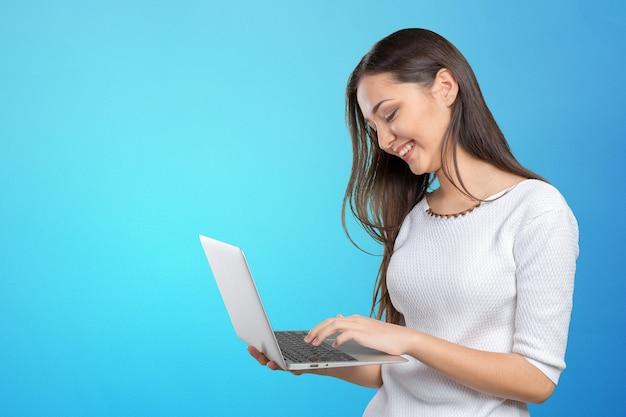 Portrait de la belle jeune femme tenant un ordinateur portable isolé