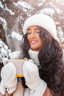 Portrait de belle jeune femme tenant une tasse avec une boisson chaude dans la forêt en hiver