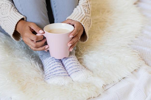 Portrait d'une belle jeune femme tenant une tasse de café chaud