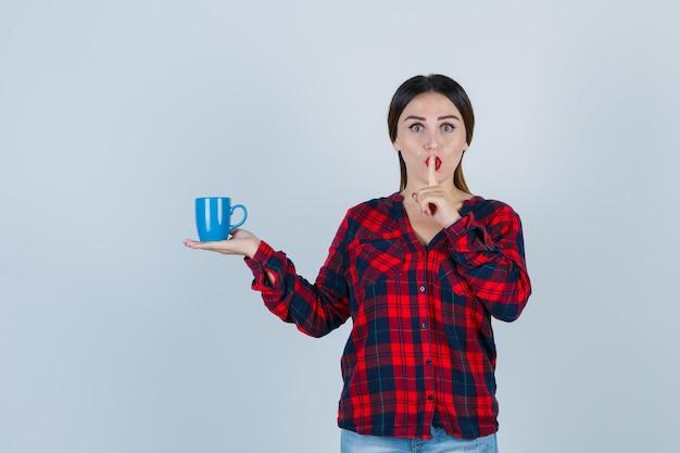 Portrait d'une belle jeune femme tenant une tasse tout en montrant un geste de silence en chemise décontractée, en jean et en regardant la vue de face focalisée