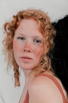 Portrait d'une belle jeune femme touchant sa tête avec des cheveux noirs