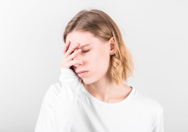 Portrait de la belle jeune femme touchant ses tempes ressentant le stress