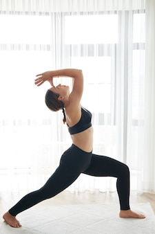 Portrait de belle jeune femme travaillant à la maison faisant du yoga ou de l'exercice de pilates debout dans