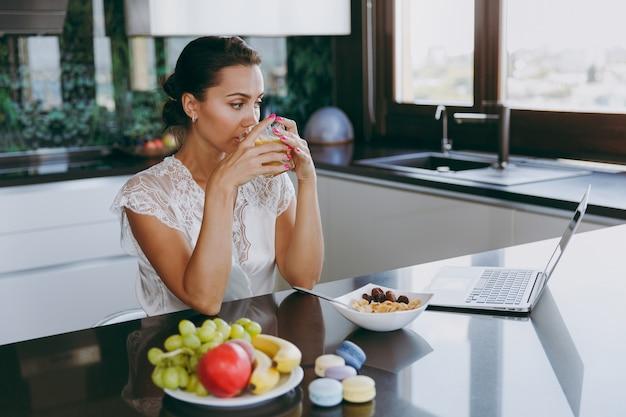 Le portrait d'une belle jeune femme travaillant avec un ordinateur portable pendant le petit-déjeuner avec des céréales et du lait et buvant du jus d'orange