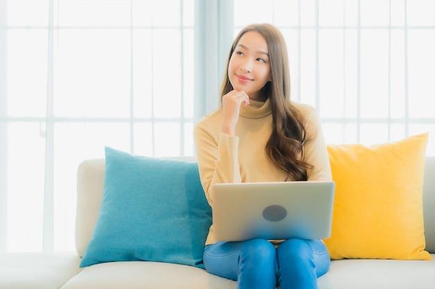 Portrait de la belle jeune femme utilisant un ordinateur portable sur le canapé dans le salon