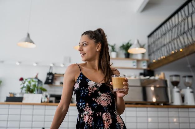 Portrait de la belle jeune femme va boire du café